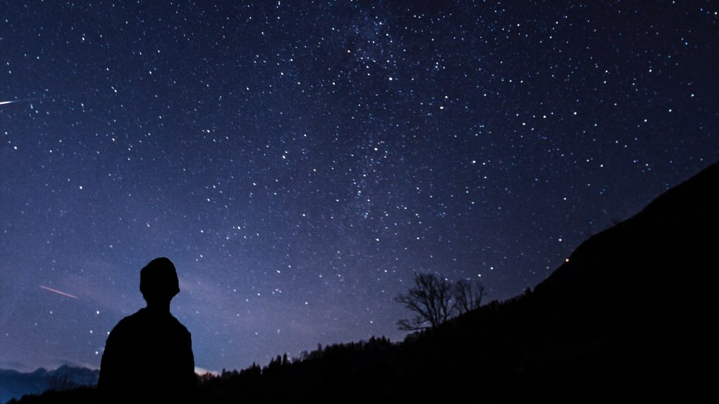 what is wellness, spiritual wellness, man looking at the milky way, cosmos, meaning of life